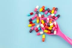 Färgrika medicinkapslar med skeden Royaltyfri Bild