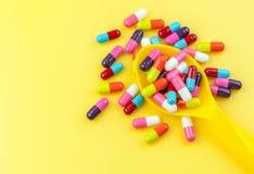 Färgrika medicinkapslar med skeden Royaltyfria Bilder