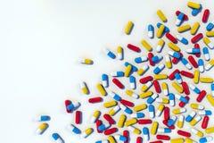 Färgrika medicinkapslar spridda på den vita tabellen stock illustrationer
