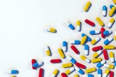 Färgrika medicinkapslar spridda på den vita tabellen vektor illustrationer