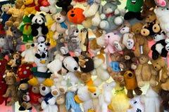 Färgrika mjuka leksaker för barn` som s hänger på rader på en marknad royaltyfri bild