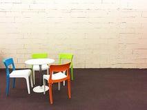 Färgrika moderna stolar på väggkvarteret lagar mat med grädde och bryner matta med Royaltyfri Fotografi