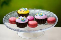 Färgrika muffin med dekorativa blommor och makron Arkivbilder