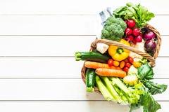 Färgrika organiska vårgrönsaker i vide- korg på trä arkivbild