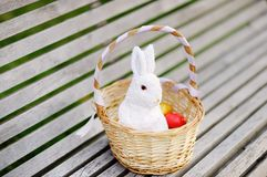 Färgrika påskägg i en korg på träbänk med den gulliga vita leksakkaninen Arkivbilder