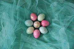 Färgrika påskägg i en turkos skyler arkivfoton