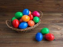 Färgrika påskägg i korg på träbakgrund Royaltyfri Foto