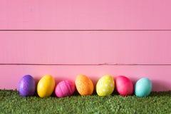 Färgrika påskägg i rad på botten av rosa bakgrund för träbrädevägg och lägga i grönt gräs med rum eller utrymme för kopia royaltyfri fotografi