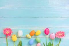 Färgrika påskägg med blommor på lantlig träbakgrund royaltyfri foto