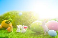 Färgrika påskägg och kaninleksaker på grönt gräs Abstrakt fantasibakgrunder med den magiska boken Royaltyfri Foto