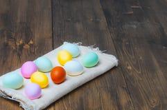 Färgrika påskägg på handduken på gammal lantlig träbakgrund Arkivbild