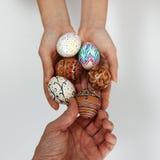Färgrika påskägg på säckväv, den kvinnliga handen valde och väljer ett ägg royaltyfri foto