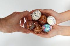 Färgrika påskägg på säckväv, den kvinnliga handen valde och väljer ett ägg arkivfoton