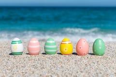 Färgrika påskägg på stranden i solig dag arkivfoto