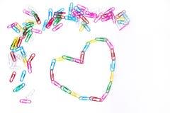 Färgrika paperclips och hjärta på viten arkivfoton