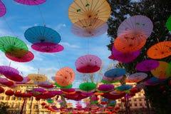 Färgrika pappers- paraplyer på himmelbakgrunden royaltyfria bilder