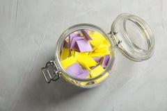 Färgrika pappers- stycken för lotteri i exponeringsglaskrus arkivbild