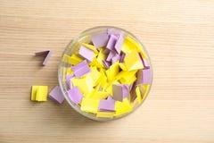 Färgrika pappers- stycken för lotteri i exponeringsglasvas på träbakgrund arkivfoton