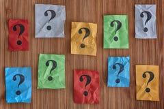 Färgrika pappersanmärkningar med frågefläckar på en träbakgrund Arkivfoto