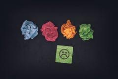 Färgrika pappersbollar och ledsen framsida på en dokument med olika förslaganmärkning Arkivfoto