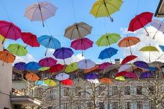 Färgrika paraplyer i den blåa himlen ovanför den gamla gatan i den Carouge staden, grannskap av Genève, Schweiz, fotografering för bildbyråer