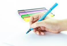 Färgrika pennor med handinnehavet Arkivfoton