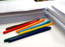 Färgrika pennor och documets på tabellen royaltyfri fotografi