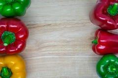 Färgrika peppar på sidan av träbakgrunden Royaltyfri Foto