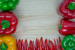 Färgrika peppar på sidan och botten av träbakgrunden Royaltyfri Foto