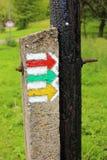 Färgrika pilar för turist- tecken på den gamla träpolgrundstötningen Fotografering för Bildbyråer