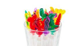 Färgrika plast- cocktailpinnar i exponeringsglas på vit bakgrundsintelligens Arkivbild