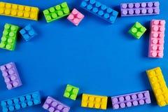 Färgrika plast- konstruktionskvarter på blå bakgrund som lurar leksakram Royaltyfri Foto