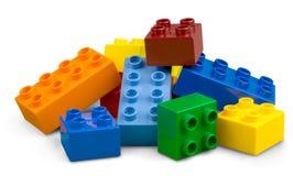 Färgrika plast- kvarter för leksak på vit bakgrund Arkivfoto