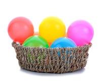 Färgrika plast- leksakbollar i korg Royaltyfri Bild