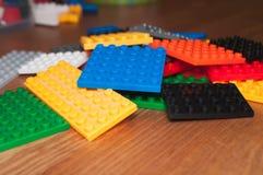 Färgrika plast- leksakkvarter på en trätabell fotografering för bildbyråer