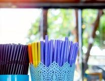 Färgrika plast- sugrör i plast- behållare i coffee shop arkivfoto