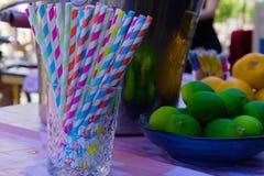 Färgrika plast- sugrör på tabellen arkivbild