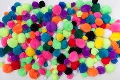 Färgrika Pom Poms på en vit bakgrund arkivfoton