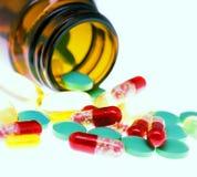 Färgrika preventivpillerar och en flaska royaltyfri fotografi