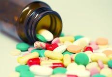 Färgrika preventivpillerar och en flaska arkivbild