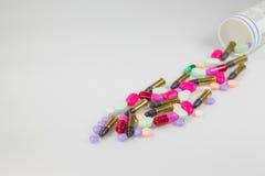 Färgrika preventivpillerar och kula på vit bakgrund Arkivbilder