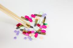 Färgrika preventivpillerar och kula på vit bakgrund Arkivfoto