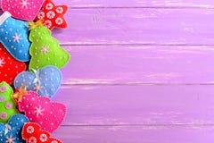färgrika prydnadar för jul Filtjulgranar, tumvanten, hjärtor, stjärnor på lila träbakgrund med tomt utrymme för text Arkivbild