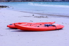 Färgrika röda kajaker på stranden Royaltyfria Bilder