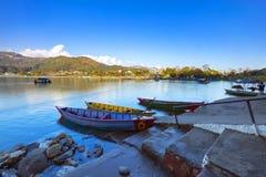 Färgrika radfartyg i Phewa sjön på aftonljus arkivfoton
