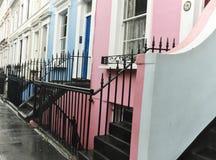 Färgrika radhus i den Notting Hill grannskapen av London, England på en våt dag Royaltyfria Foton