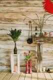 Färgrika regnkängor med våren blommar, stearinljus, stenar, olil l Arkivfoton