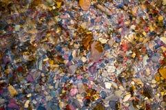 Färgrika Rocks i klart vatten Fotografering för Bildbyråer