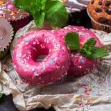 Färgrika rosa donuts på en rostig tabell för grunge Arkivfoton