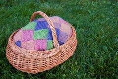 Färgrika rosa färger, gräsplan, blått, apelsin, stack ullkoftan i träkorg på bakgrunden för grönt gräs Lantlig ull Öppen luft fotografering för bildbyråer